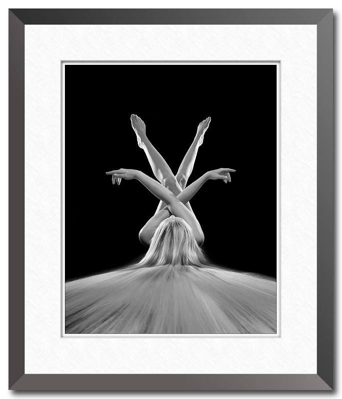 Black and white fine art photo by Craig Stocks showing a nude female with arms and legs crossed and hair flowing