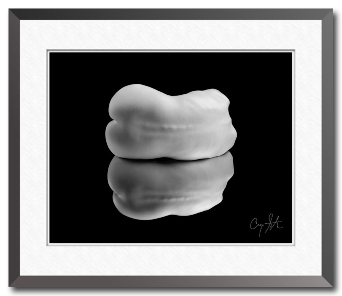 Black and white photo of a nude female's torso curled into the shape of a jellybean and reflected in a mirror, fine art photo by Craig Stocks