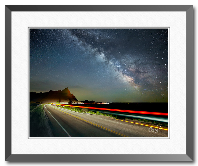 Night photo showing the Milky Way over Badlands National Park with streaks of light in the foreground from a passing car.  Fine art photograph by Craig Stocks