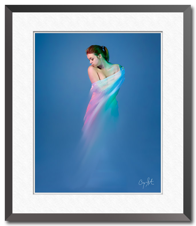 Fine art photo with digital paint effects of a woman wrapped in white cloth against a blue background. Photo by Craig Stocks
