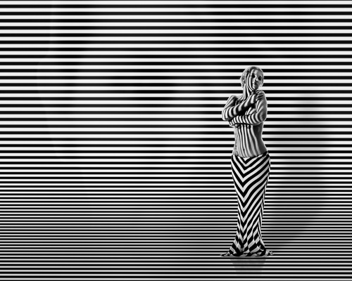 Woman with stripes and hidden face in background